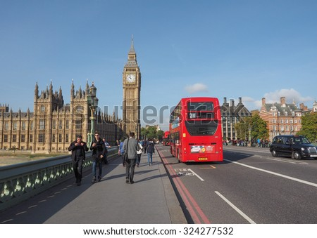 LONDON, UK - SEPTEMBER 28, 2015: Tourists on Westminster Bridge at the Houses of Parliament aka Westminster Palace - stock photo