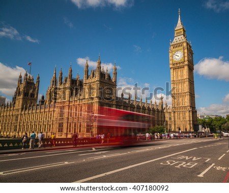LONDON, UK - 21ST JULY 2015:  Big Ben in Westminster with red London Buses going past during the day. People can be seen. - stock photo