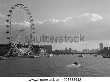 LONDON, UK - 1ST MARCH 2014: A view up the Thames during the day showing a boat in the water and the London Eye at the side - stock photo
