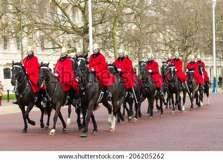 LONDON, UK - 8TH MARCH 2014: Horse Guards on horseback walking down The Mall towards Buckingham Palace during the day - stock photo
