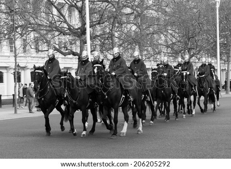 LONDON, UK - 8TH MARCH 2014: Horse Guards on horseback walking down The Mall towards Buckingham Palace during the day
