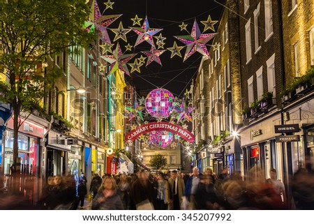 LONDON, UK - 27TH NOVEMBER 2015: Lights down Carnaby Street in London during the Christmas Season. Large amounts of people can be seen. - stock photo