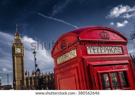 London, UK - Traditional British red telephone box with Big Ben on a sunny day with dark blue sky - stock photo