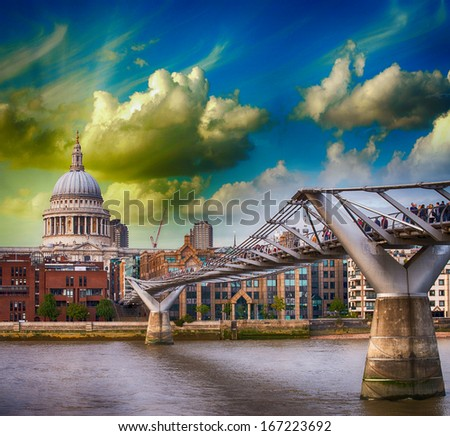 London, UK. Wonderful side view of Millennium Bridge at sunset, Saint Paul Cathedral on background. - stock photo
