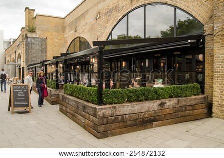 LONDON, UNITED KINGDOM - AUGUST 28, 2014:  Customers enjoying lunch at the popular Beagle cafe under the railway arches in Hoxton, East London.  The trendy area is popular with hipsters. - stock photo