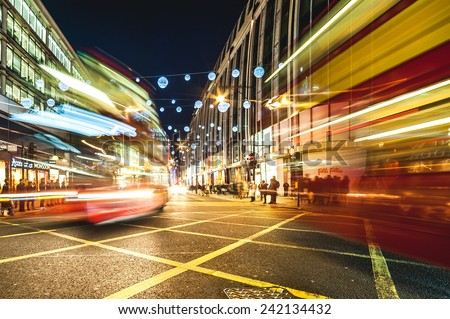 LONDON, UNITED KINGDOM- December 29: Blurred London Buses and Christmas Lights Display on Oxford Street on December 29, 2014 in London, UK - stock photo