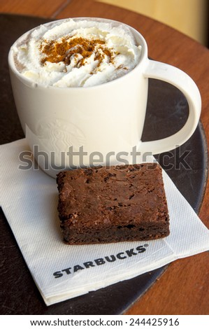 LONDON, UNITED KINGDOM - FEBRUARY 16, 2014: Cup of hot chocolate and brownie cake in in Starbucks coffee in London on February 16, 2014, UK - stock photo