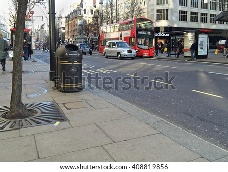 LONDON, UNITED KINGDOM - FEBRUARY 08: Oxford Street traffic with red bus and black cab in London, United Kingdom - February 08, 2015; Famous London Oxford Street with pedestrians and public transport.