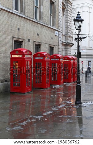 LONDON, UNITED KINGDOM - JANUARY 19: Red Telephone boxes in London on JANUARY 19, 2013. Gas Lighting and Five red telephone booths at West End in London, United Kingdom. - stock photo