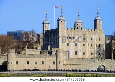 LONDON, UNITED KINGDOM - JANUARY 24, 2015: The Tower of London bathed in golden late-afternoon sunshine, with a line of tourists waiting to enter near the Traitors' Gate. - stock photo