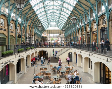 LONDON, UNITED KINGDOM - June 15 2015: Visitors in Apple Market in Covent Garden in London, UK. The Apple Market is sells arts and crafts dedicated to antiques and collectables items.