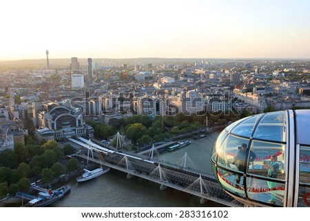London, United Kingdom - May 13: Tourists making photos and enjoying sightseeing of British capital looking at city landmarks from the cabin of the London Eye wheel on May 13, 2015 in London, UK