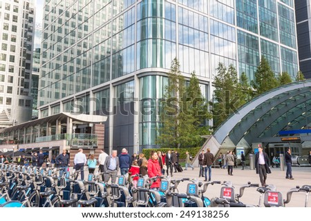 LONDON, UNITED KINGDOM - OCTOBER 30, 2013: Canary Wharf district with Barclays Cycle Hire docking station and Underground entrance. Many people, tourists and commuters, are walking in the square. - stock photo