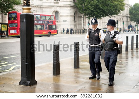 London, United Kingdom - October 2, 2013: London police walking on the sidewalk in the district of Westminster - stock photo