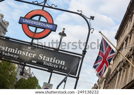 LONDON, UNITED KINGDOM - OCTOBER 30, 2013: Underground Westminster Station entrance and a building facade with United Kingdom flag, also known as Union Jack - stock photo