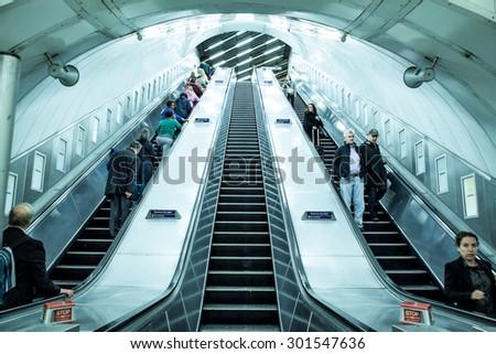 LONDON, UNITED KINGDOM - OCTOBER 8, 2014:  View of escalators and travelers inside London Underground - stock photo