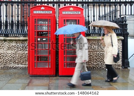 London, United Kingdom - red telephone boxes in wet rainy weather. Wet pedestrians with umbrellas. - stock photo