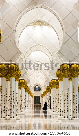 Lone Arabian woman along the Interiors of Sheikh Zayed Mosque, Abu Dhabi, United Arab Emirates - stock photo