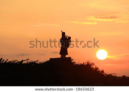 Lone bagpiper on a hill at sunset