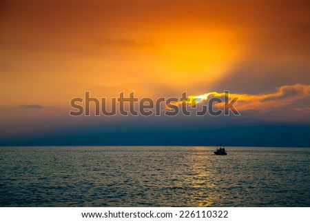 Lone boat in the sea at the beautiful sunset - stock photo