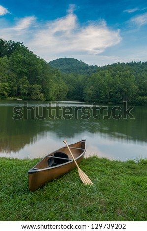 Lone boat sitting on the shore of a Western North Carolina lake ready for recreation near the Blue Ridge Parkway in Asheville, NC. - stock photo