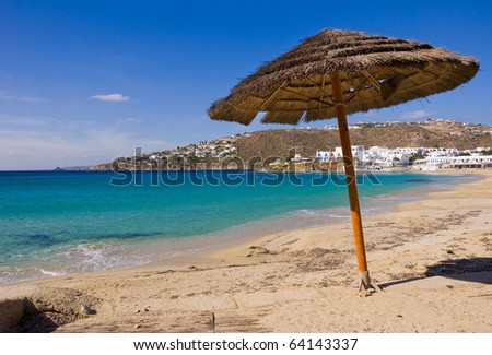 Lone Cane umbrella on the beach near the blue sea ... - stock photo