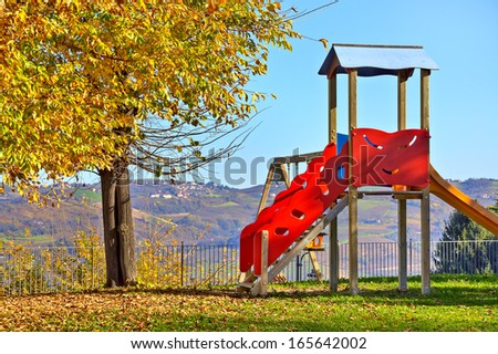 Lone children's slide on empty playground in autumn in small town of Diano D'Alba, Italy. - stock photo