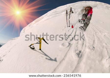 lone climber at the summit of severe weather conditions on the background of winter high mountains, among the alpine steep slopes and sharp ridges. Security against wind and avalanches - stock photo