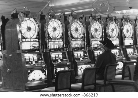 lone cowboy in black sitting at empty row of slot machines lined up - stock photo