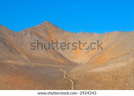 Lone Dirt Road in the Mountain Desert of Death Valley.  Mountain Range Landscape in Death Valley National Park, California, USA
