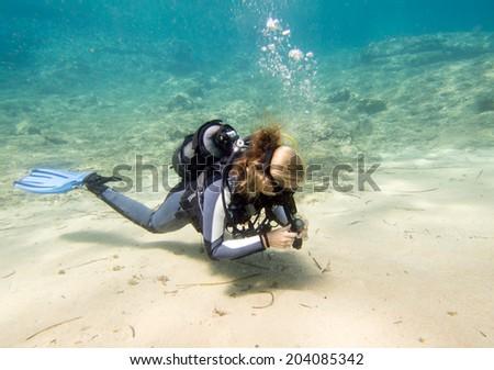 Lone female scuba diver on a dive - stock photo