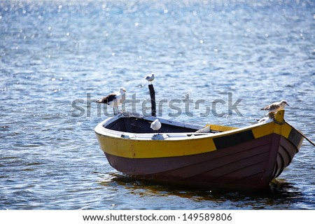 Lone fishing boat floating on the sea - stock photo