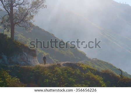 lone hiker on misty trail over looking beautiful and romantic tropical mountain.  - stock photo