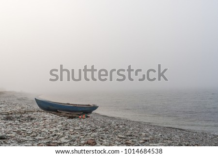 Lone landed rowboat at seaside by a foggy coast at the swedish island Oland in the Baltic Sea