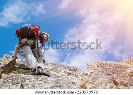 Lone male mountain climber on summit - stock photo