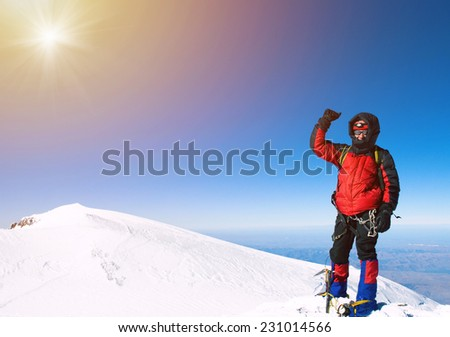 Lone male mountain climber  on the summit - stock photo