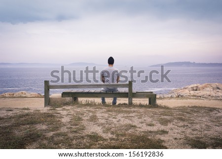 Lone man sitting in front of sea.
