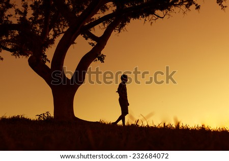 Lone man walking in a field - stock photo