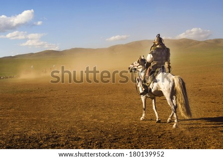 Lone Mongolian Man on a Horse in The Dessert - stock photo