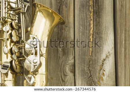 Lone old saxophone leans against wooden fence outside jazz club - stock photo