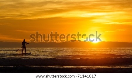 lone paddle board surfer at sunset - stock photo
