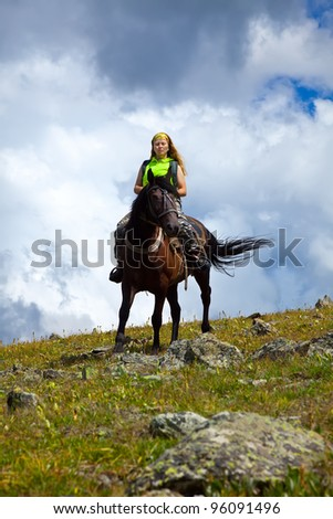 lone rider on horseback at mountains - stock photo