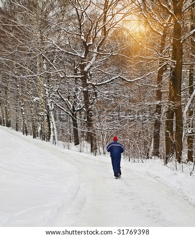 lone runner in wintry wood - stock photo