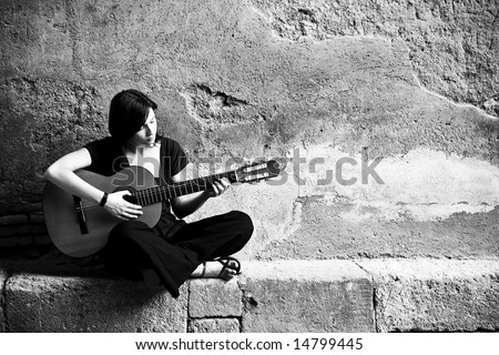 Lone sad guitarist playing in old brickwall. - stock photo