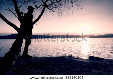 Lone sportsman looking at colorful  sunset on shore of autumn lake. Silhouette  stand bellow birch tree.
