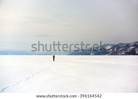 Lone stranger walking his path in the middle of snow white nowhere with distant mountains in background - stock photo