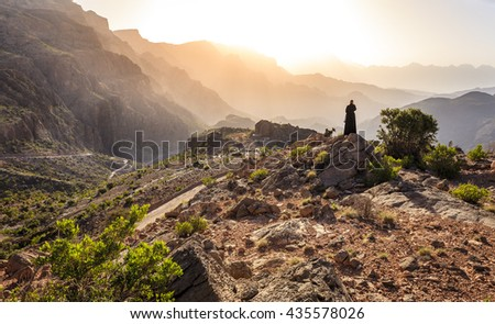 Lone woman in abaya in Al Hajar Mountains of Oman at sunset