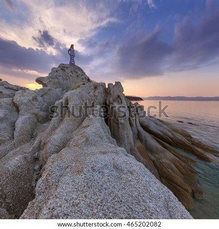 Lone woman standing on cliff and watching the setting sun from the shore with strange rocks. Coastline of Aegean Sea, Greece.