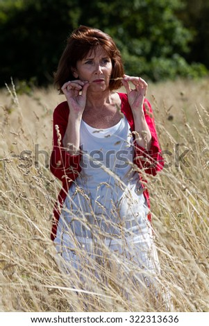 loneliness in countryside - beautiful 50s woman in reflection alone in long dry field or meadow,natural summer daylight - stock photo
