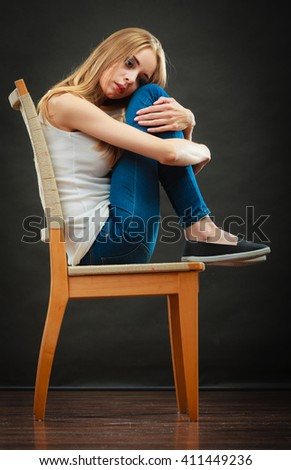 Loneliness negative emotion concept. Young sad lonely woman sitting huddled on chair - stock photo